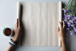 Dos manos desplegando un pergamino